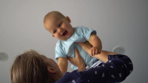 Woman lifts up and shakes her laughing baby. Low angle shot Footage