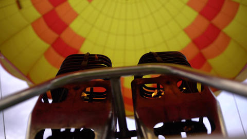 Fire of hot air balloon burner and bright yellow envelope. Low angle handheld Footage