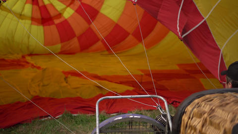 Hot air balloon burner flames up and inflates colorful envelope. Handheld shot Footage
