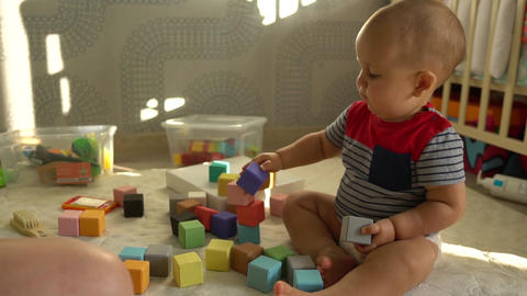 Cute toddler boy plays with colorful baby blocks sitting on a floor. Slow motion Footage