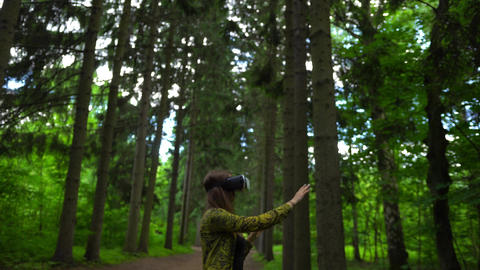 Green park and woman in VR helmet playing with virtual reality Live Action