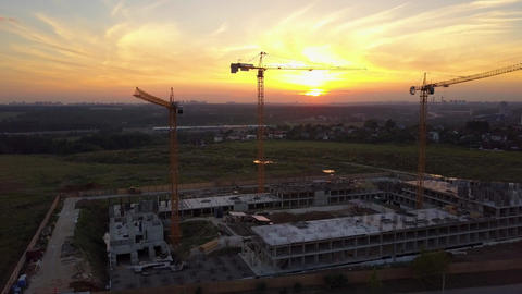Aerial shot of building site with cranes against sunset sky. Drone moves upwards Footage
