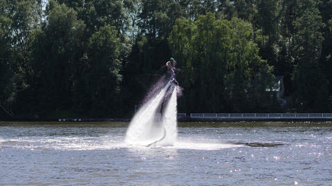 Hydroflyer makes spins on flyboard producing water splashes Image
