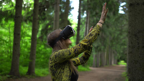 Woman in VR headset touches the air by hands. Virtual reality among trees Footage