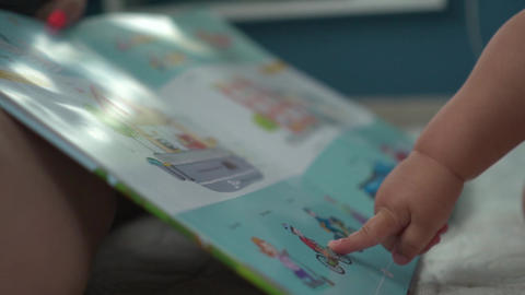 Baby points with his finger to cyclist drawing in illustrated book Archivo