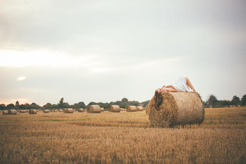 Beautiful Girl Lying on a Bale of Hay in the Field Foto