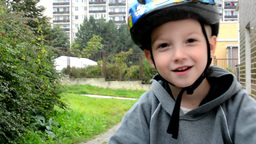 Child (a little boy) rides bike and smiles - in the background houses and nature Footage
