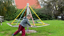 child (a little boy) plays on the playground - roundabout Footage