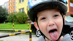 child (a little boy) grimaces - child with helmet (bike) - house and car in back Footage
