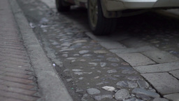 Cobblestone and Flagstone Road Cars Passing Low Angle Footage