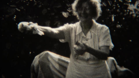 1943: Crazy grandma holding up chickens passing them out to grandpa Footage
