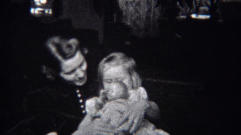 1944: Mother daughter rocking chair with baby doll and big smiles Live Action