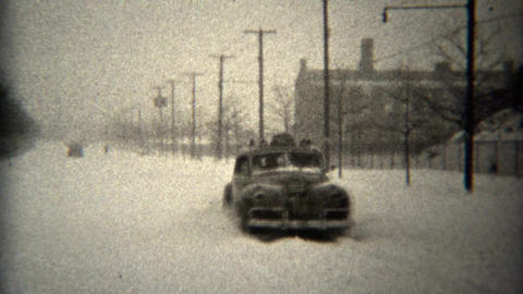 1944: Cars driving unplowed winter snow covered streets sliding around Footage