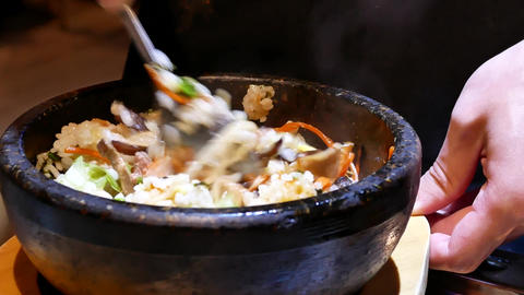 Motion of waiter stirring Korean bibimbap for customer on table inside Korean Live Action