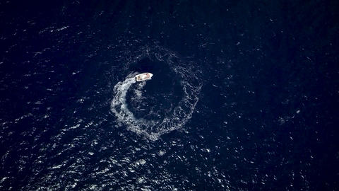 Aerial view of a motor boat designing a circle in the sea navigating fast Archivo