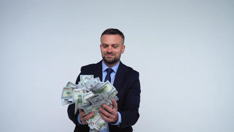 Man is smelling, throws and enjoys the falling dollar bills. Slow motion Footage