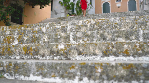 Busy woman uses a smartphone while running down the stairs outdoors Footage