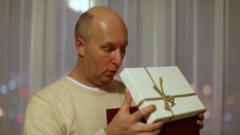 Adult caucasian man open gift box and surprised. A surprised and delighted man Footage