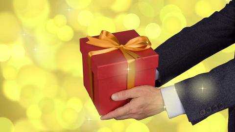 Two male hands holds red gift box with gold bow. Celebrate eve present gift box Live Action
