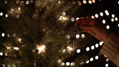 Hand of female touching Christmas tree with bokeh lights in Christmas time ビデオ