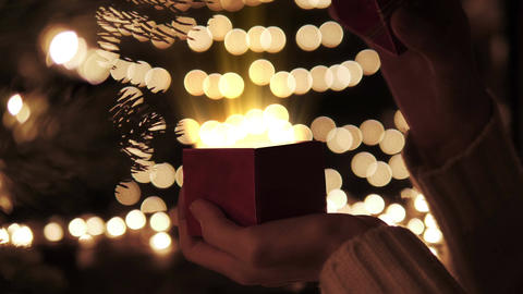 Woman open red Christmas gift box with golden magic lights Live Action