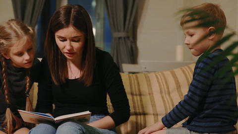 Mom sitting on the couch with his daughter and young son, reading them a story Footage
