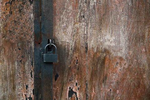 Close up rustic padlock hanging on a door Fotografía