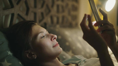 Close-up of young smiling woman using smartphone lying in bed at home at night Footage