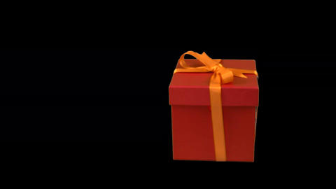 Red gift box with yellow gold ribbon bow dolly in track in zoom in at Live Action