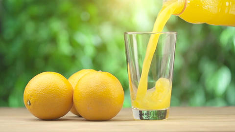 Orange juice pouring in glass on green summer background Footage