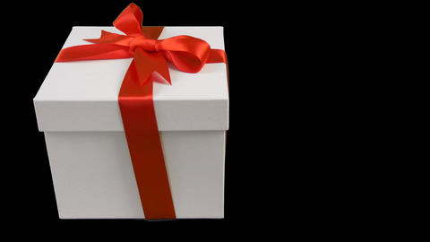 White gift box with red ribbon bow stands at black background. Track to right Image