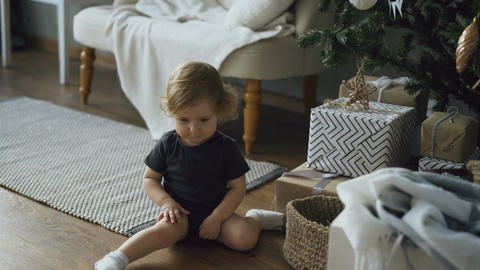 Adorable little girl playing with toy balls sitting near Christmas tree at home Archivo