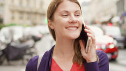 Smiling businesswoman standing on street talking on mobile. Professional female ビデオ