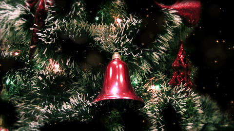 Close up of decorated Christmas tree at night with red bell, flashing garlands Animation