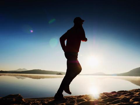 Man running at morning sea. Each day morning workout Photo