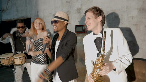 Four musicians perform in a nightclub. A beautiful white girl is dancing. A Image