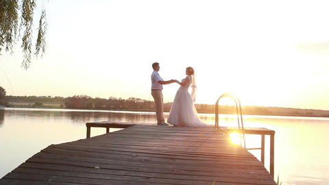 Newlyweds standing on the wharf near the lake at sunset Footage
