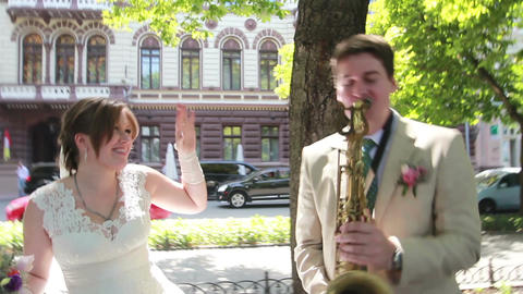 A couple of newlyweds are fooling around playing on the saxophone at the street Footage
