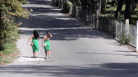 Girls dressed in green dress walking on a street 6a Footage