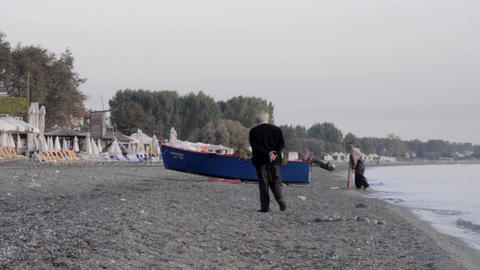 Old man who was walking on the beach going towards a boat pulled ashore 6b Footage