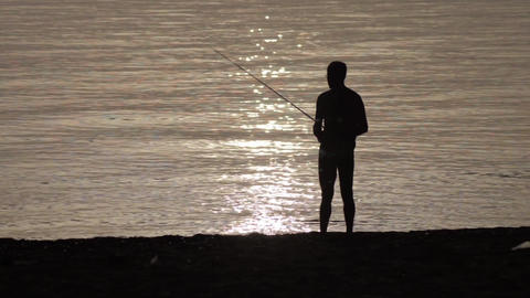 Silhouette Of A Man Came Out From Fishing At Ocean In The Early Hours Of The Mor stock footage