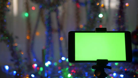 smartphone with a green screen on a new years background the man lights a