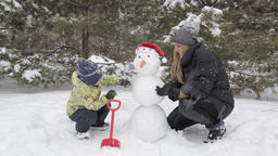Mom and son make a snowman 11 Footage