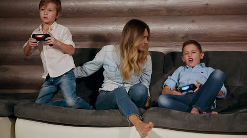Mother and two sons sitting on the sofa in his house playing video games with Footage