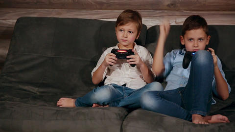 Two brothers sitting on the couch and very emotional playing video games with Footage