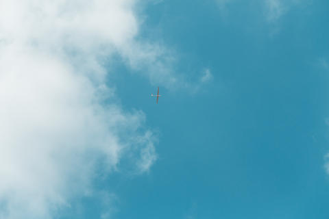 Glider gliding in blue sky from below Photo