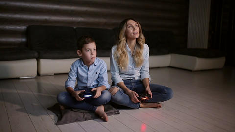 Beautiful mother with her son playing video games on gaming console in the Live Action