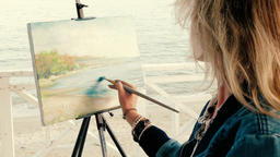 Young blonde woman artist painting seascape on the beach Footage