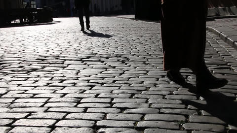 Harsh shadows of feet on the pavement. light on the stone pavement Footage