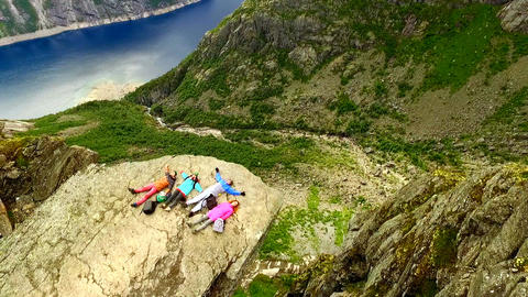 Norway. Two guys and two girls are lying on the edge of the cliff. Trolltunga Live Action